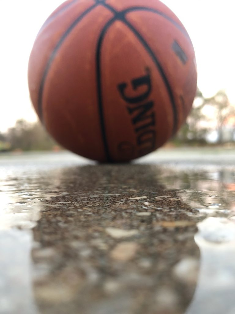 Closeup of basketball and its reflection in a puddle