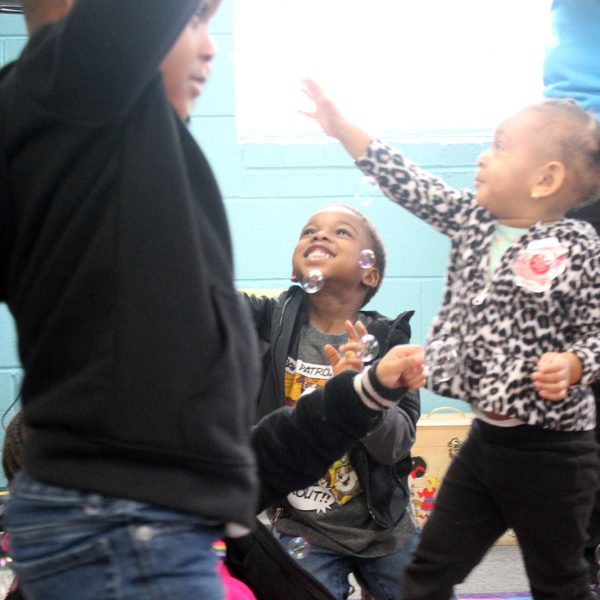 Small children reaching to catch bubbles during storytime