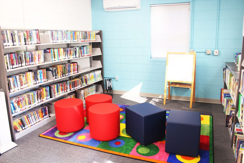 Children's area at Bragtown featuring comfortable seating, a colorful rug, shelves of children's books, and an easel