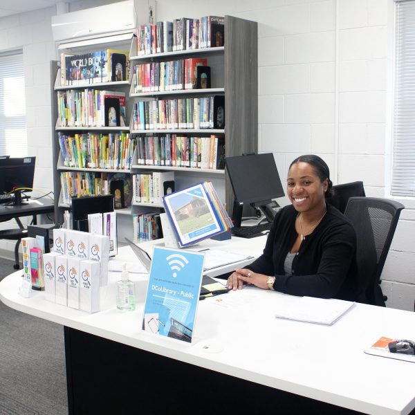 Bragtown's manager sitting at the info desk, with brochures and other info ready and shelves of books along the back wall