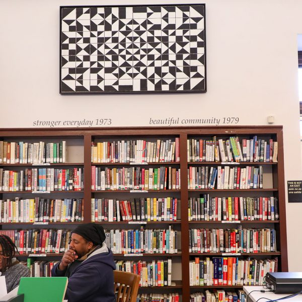 Two people work together at a public computer, with wooden bookcases, abstract art, and phrases related to the branch's history on the wall behind them