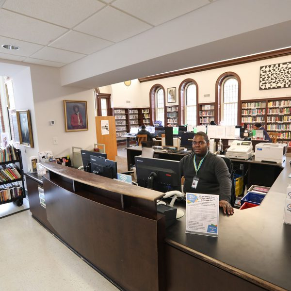 A library staff member sitting at the checkout desk, with the main reading room in the background