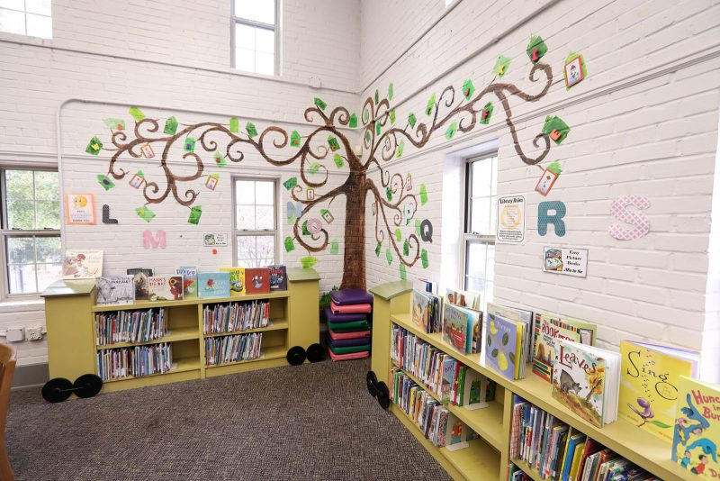 Corner in the children's area with low colorful shelves of books and a tall tree mural branching overhead