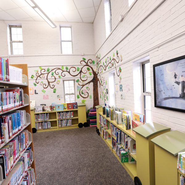 Tree mural in the corner of the children's area, in the background past bookshelves and posters