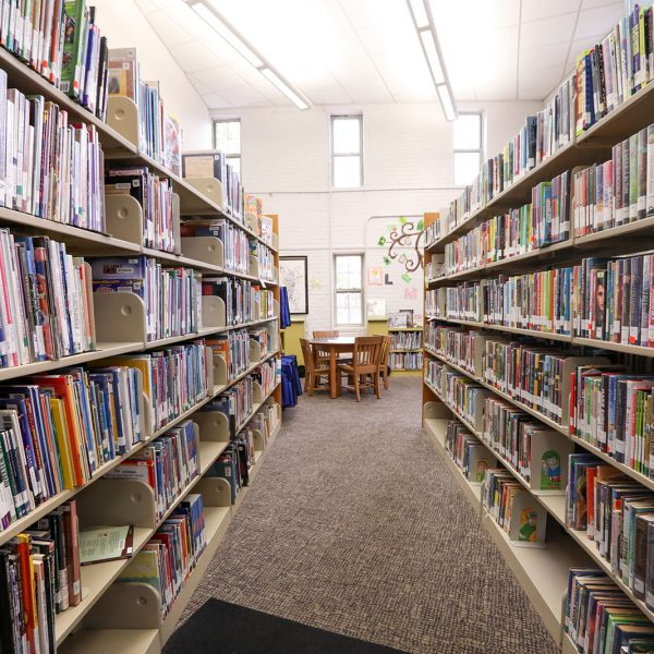 Row of bookshelves in the children's area, with a table and chairs at the end