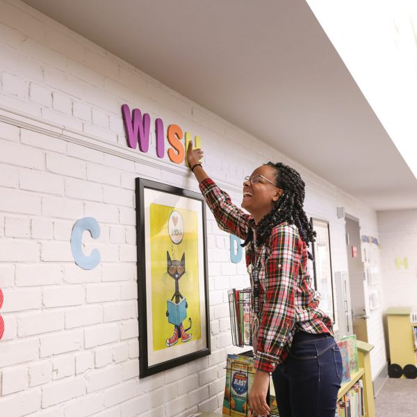 """A children's librarian laughs while hanging up foam letters spelling """"wish"""" on the wall"""