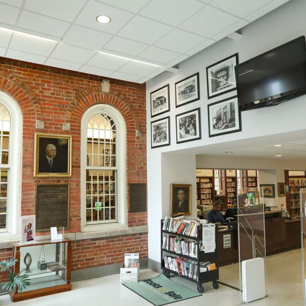 The building lobby, with paintings, photographs, and an entryway into the main space of the building
