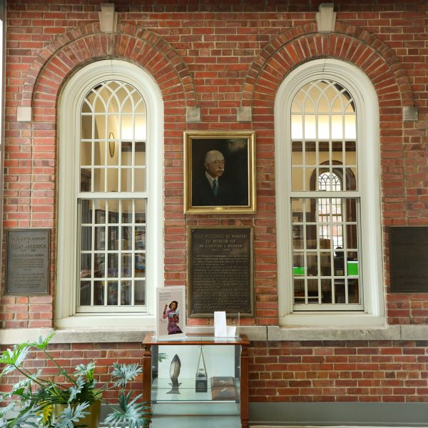 Painted portrait of Dr. Stanford L. Warren hanging above a plaque explaining that the building was named in his honor, set on a brick wall between two decorative interior windows