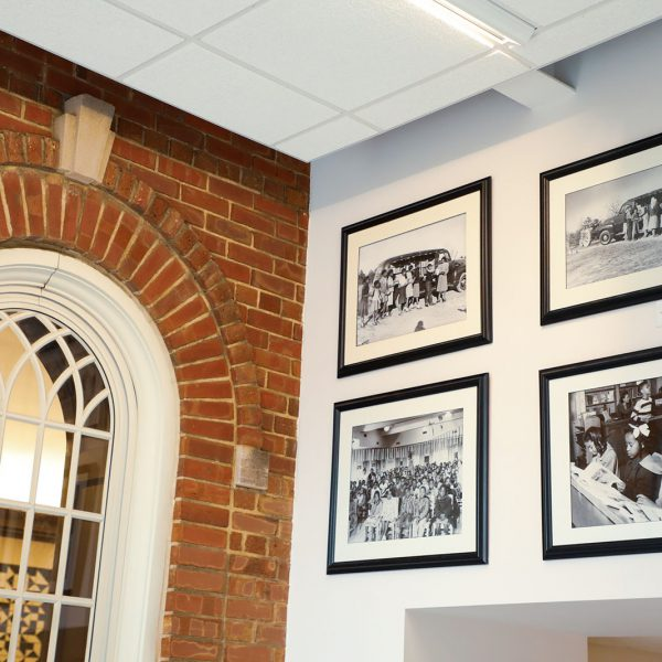 Framed black-and-white photographs with scenes from Stanford L. Warren's history hanging on the lobby walls