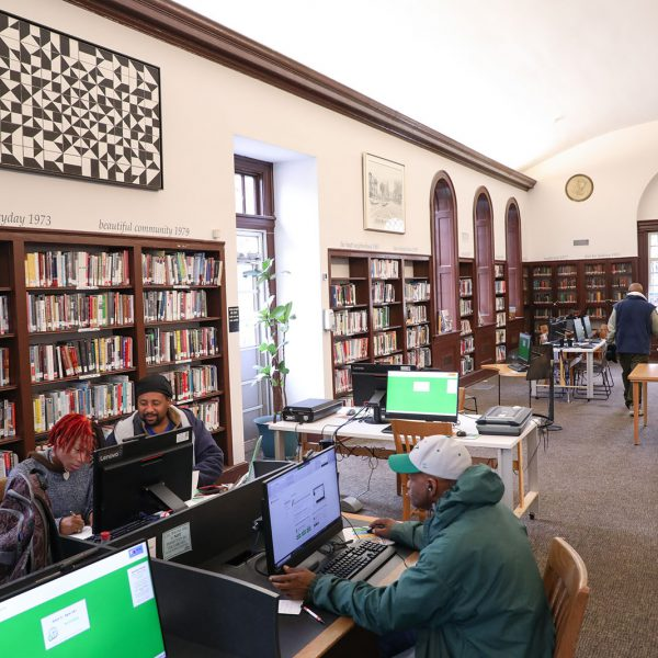 The main reading room at Stanford L. Warren, with people using public computers, tables and chairs, and bookshelves lining the walls
