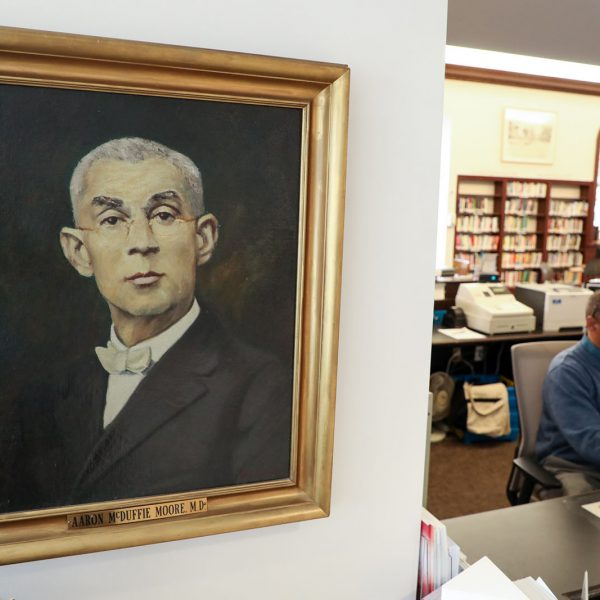 Painted portrait of Aaron McDuffie Moore, M.D., with the checkout desk and library staff visible in the background