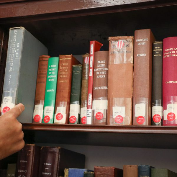 A hand reaches to pull an old book from a shelf behind an opened cabinet door
