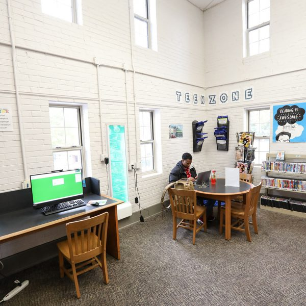 """Corner labeled """"Teen Zone,"""" with a person sitting at a table using a laptop, a public computer station nearby, and shelves of DVDs"""