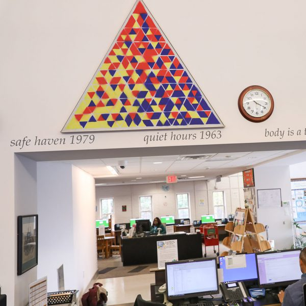 All the Possibilities of Three Into Four, by Vernon Pratt - a large, triangular, red yellow and blue painting with many geometric shapes. It hangs on the wall above an opening with the main checkout desk below and the children's area across the lobby