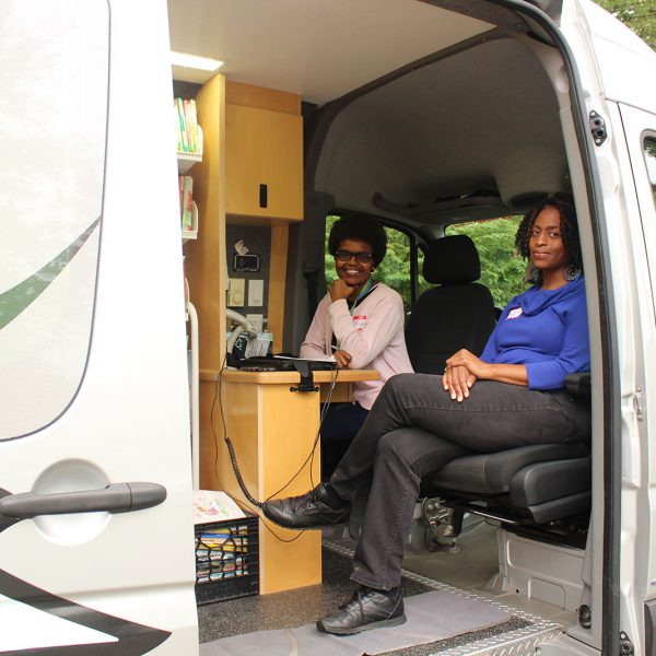 Outreach staff seated at the front of the Bookmobile, ready to help check out books