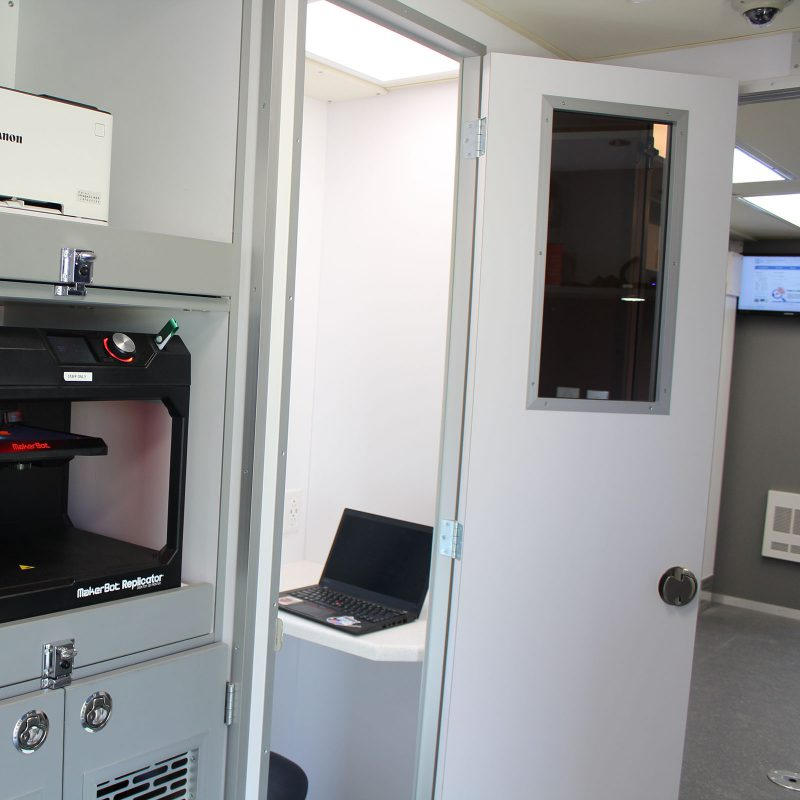 Small booth-like space with the door open and a laptop on the counter