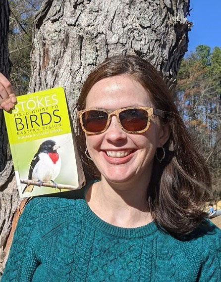 Barbara in front of a tree, holding up the Stokes Field Guide to Birds