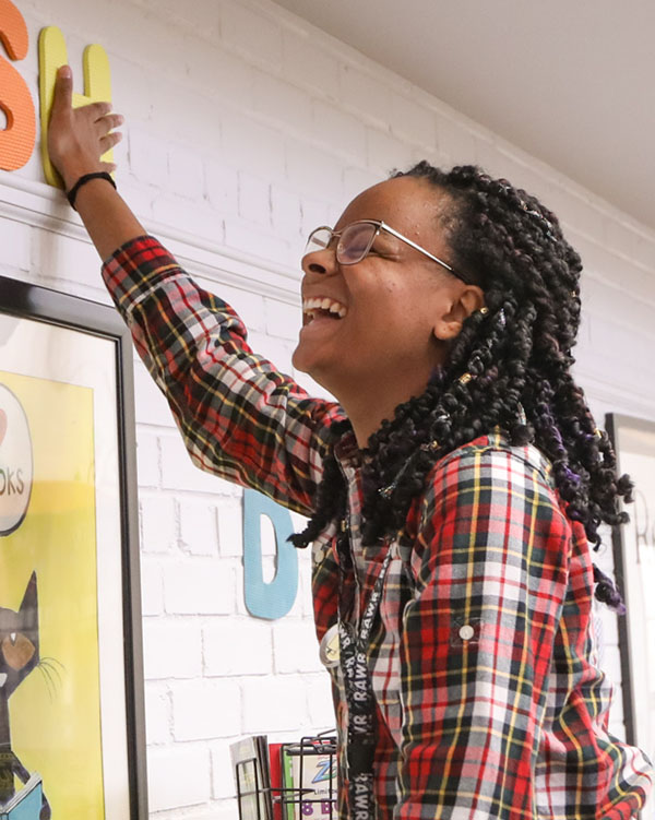 """Ms. Danielle laughs while hanging up the last letter in a wall decoration saying """"wish"""""""