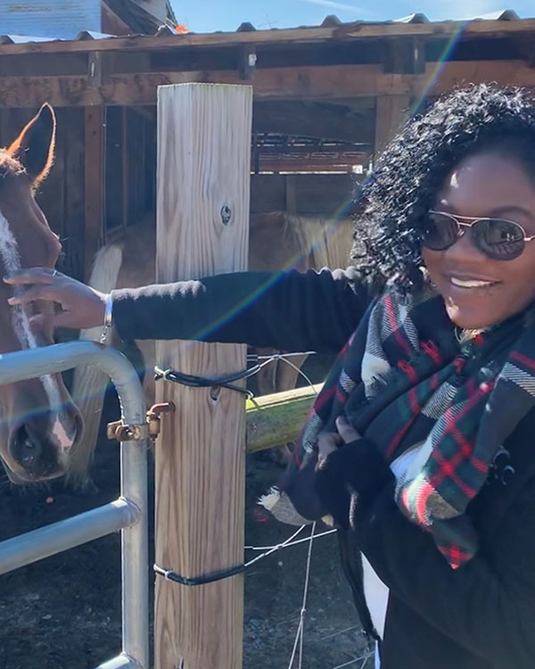 East Regional children's manager Diamond petting one of the equine stars of East Regional's Storytime with Horses