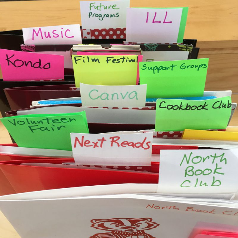 Tagged file folders representing Emily's many library interests and activities, including book clubs, the volunteer fair, and more