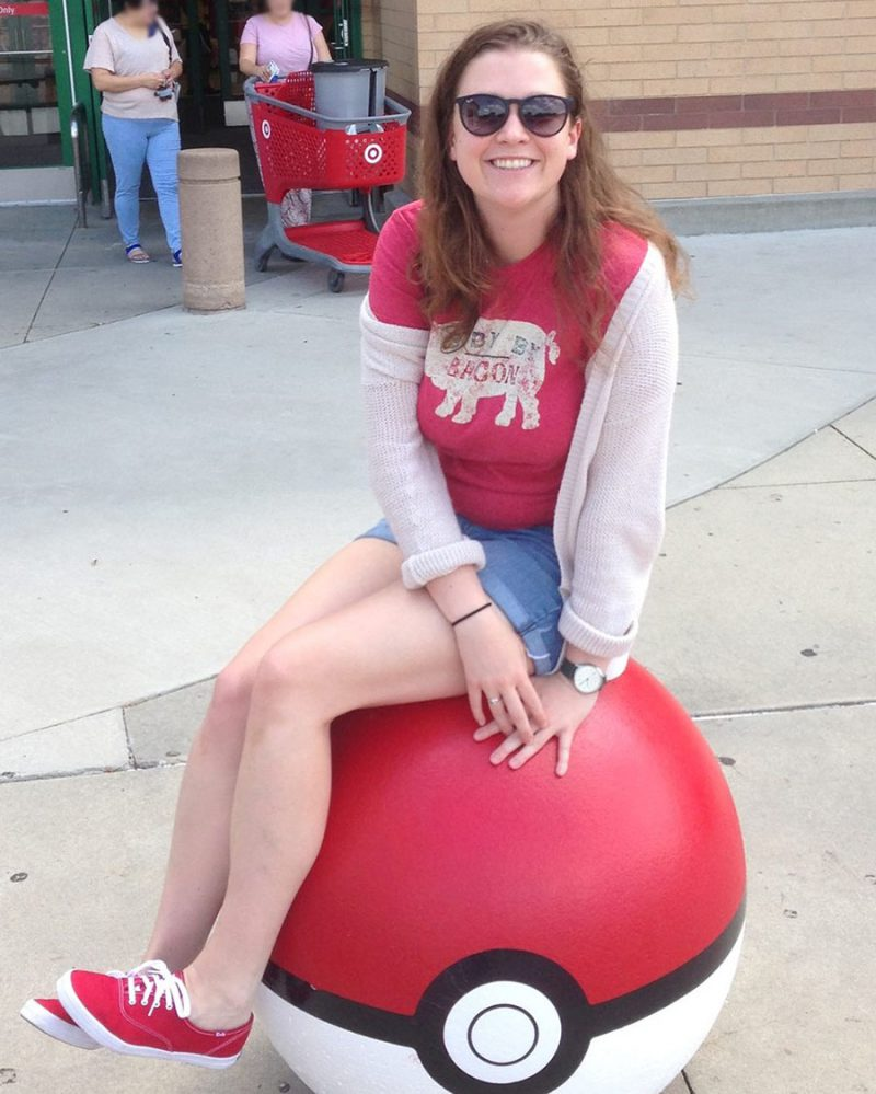 Julia sitting balanced on top of life-sized Poke Ball