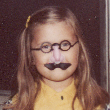 Laura as a child, wearing the classic glasses-nose-and-mustache costume