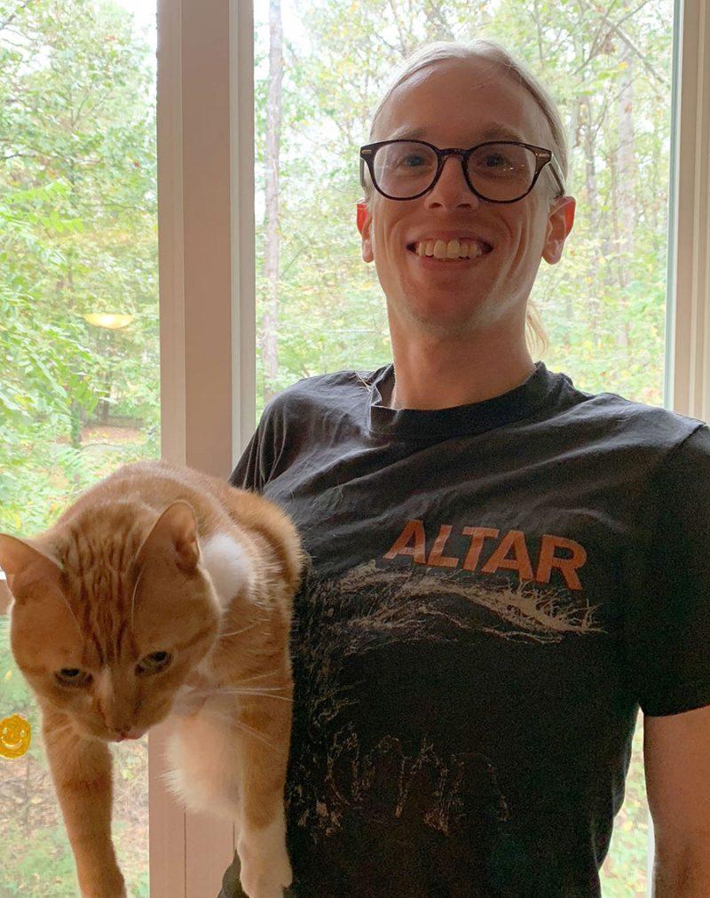 Scott holding up a large orange cat
