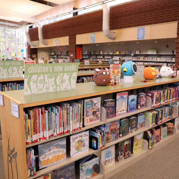 Shelf of children's picture books, with a line of pumpkins decorated to look like different characters along the top and more shelves in the background