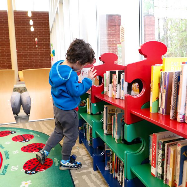 Young child browsing board books on a low, colorful shelf