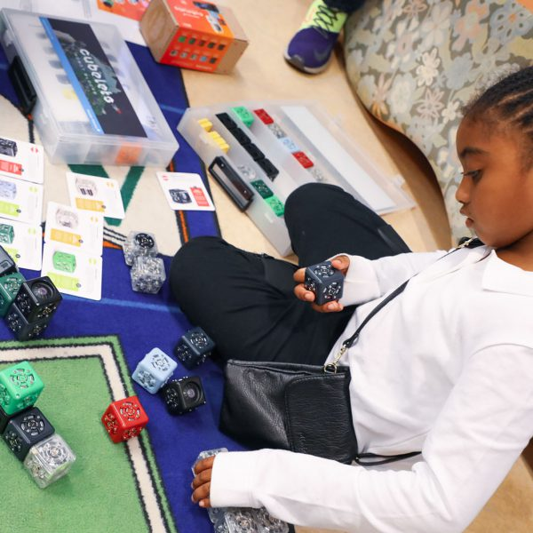 A child sits on a colorful rug and plays with a modular robotics block set