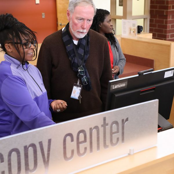 Librarian helping a woman with a computer behind a sign that says Copy Center