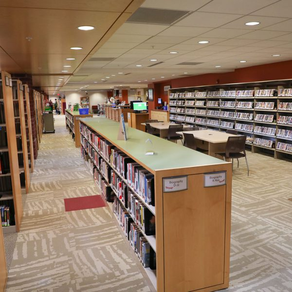 The open front area at East Regional, with shelves of books and DVDs, large tables with chairs, and the checkout desk in the backgroud