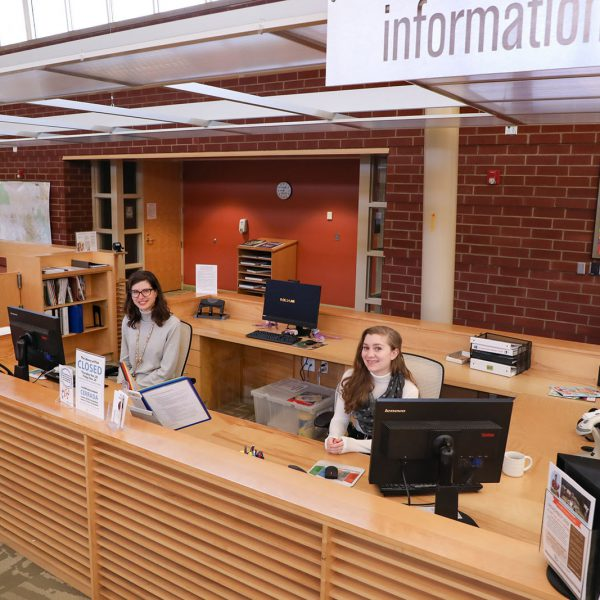 """Librarians sitting at computers at a large desk under a sign that says """"Information"""""""
