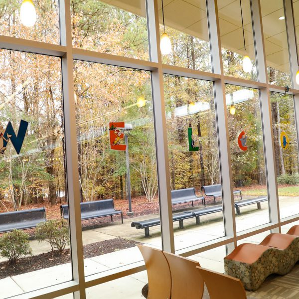 """Wall full of tall windows. Each pane has a letter with a Dr. Seuss character, spelling out the word """"Welcome."""" Seating is available indoors and out."""