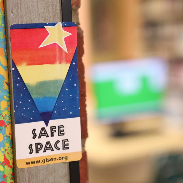 """Colorful sign saying """"Safe Space"""" posted in a door frame"""