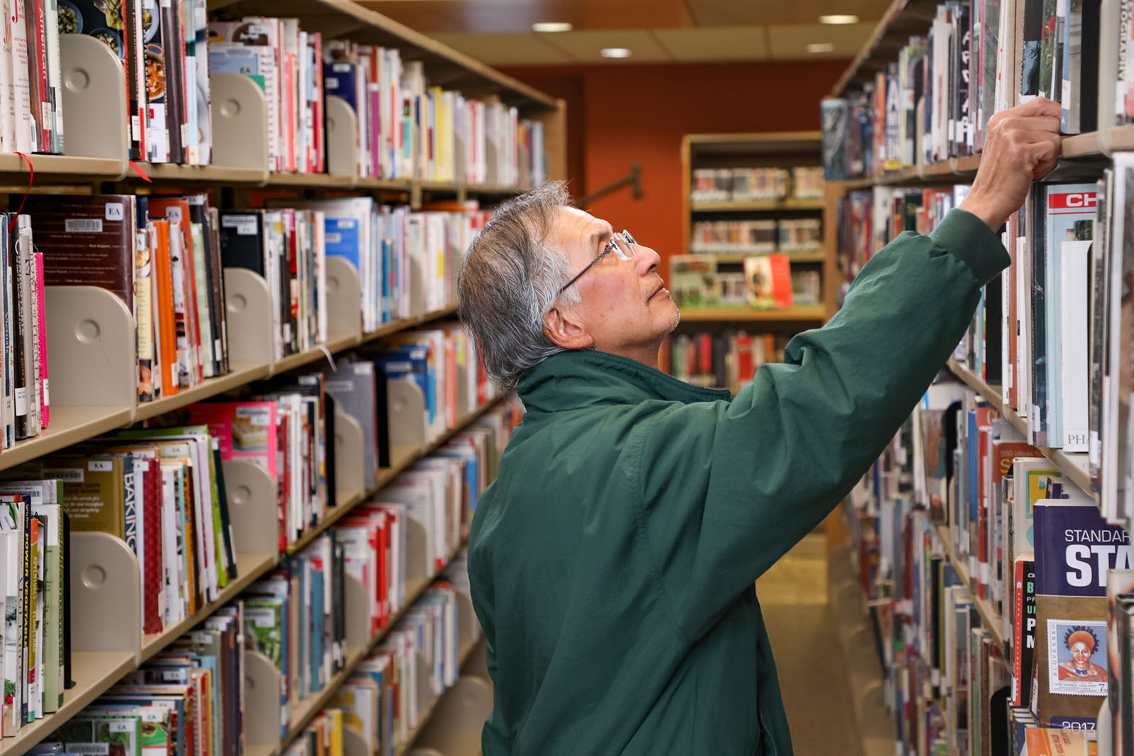 A man stands in the aisle between two bookshelves and reaches up to take down a book