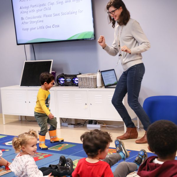 Librarian and small child dancing at the front of the room as other children watch