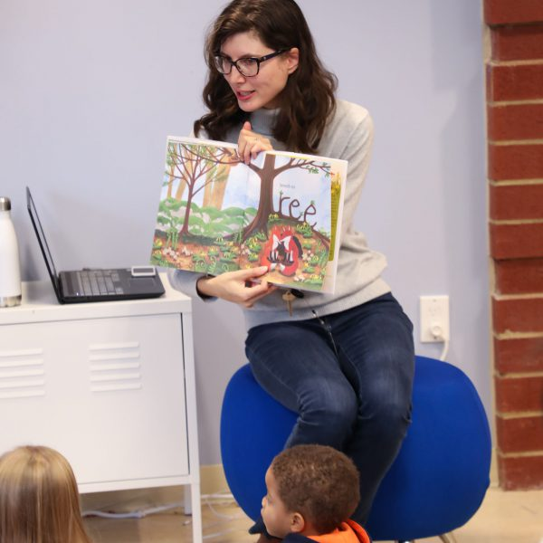 Librarian at the front of the room holding up a picture book as a group of seated children watch