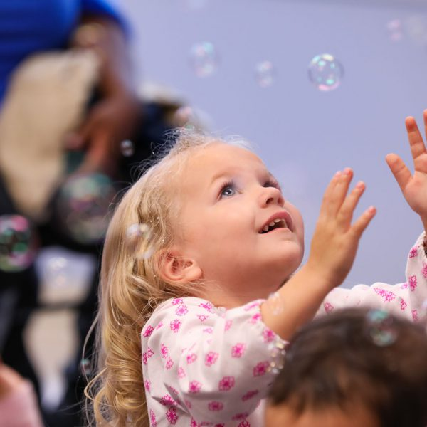 Young child reaching up to catch bubbles