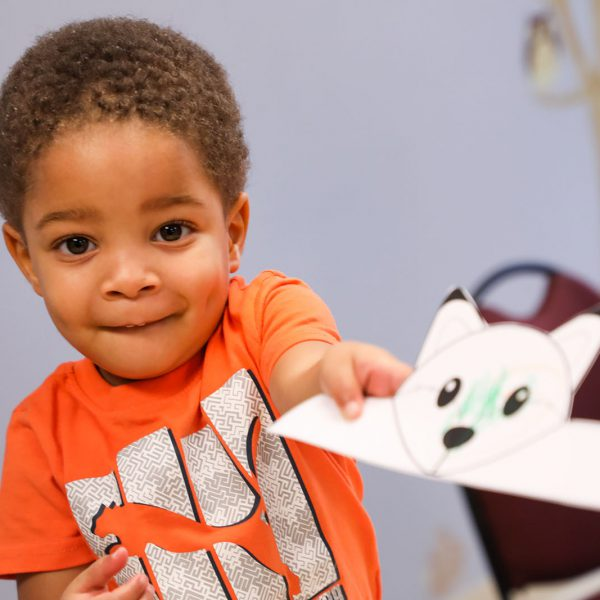 Young child holding up a paper fox headband he's been coloring
