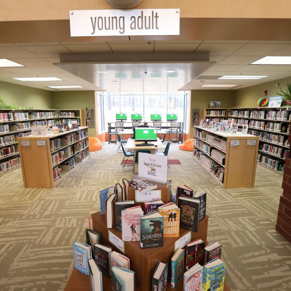The teen area of East Regional Library, with a display of new teen fiction books at the entrance, walls lined with bookshelves, and computers lined up by a large window at the back wall