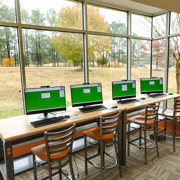 Computers in the teen area at East Regional Library, lined up in front of a large window looking out onto a natural area