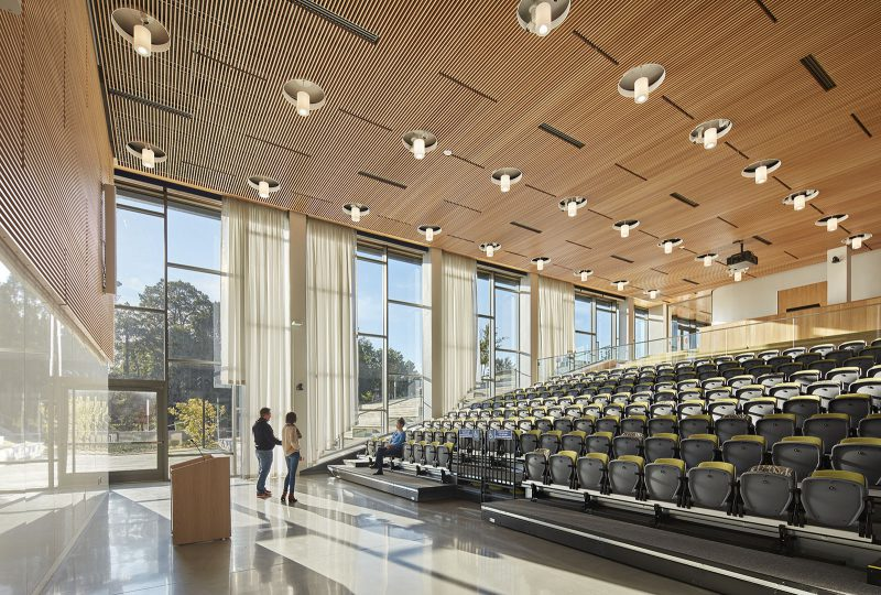 Large auditorium with rows of folded seats, a podium at the front, and a wall of tall windows to the side