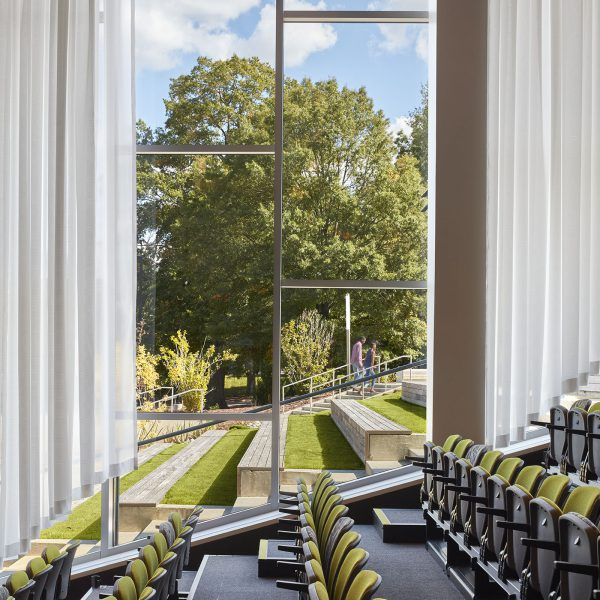 Rows of folded auditorium chairs. Outside the window, grassy amphitheater seating follows the slope of the indoor auditorium