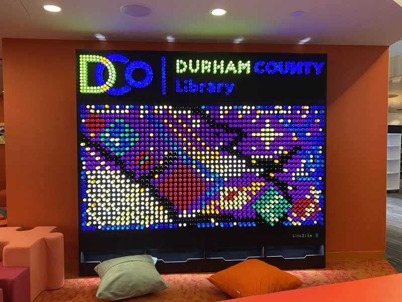 Six-foot-tall light wall, with the Durham County Library logo and an abstract design created in light pegs