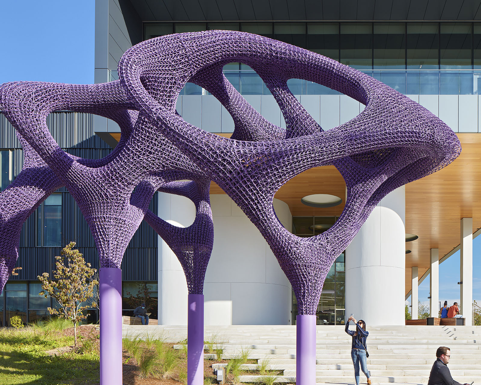 A large, purple, abstract sculpture standing in front of the building
