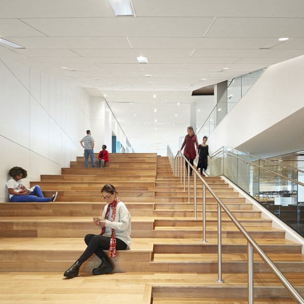 Divided staircase with steps and railings on one side, wooden bench seating on the other