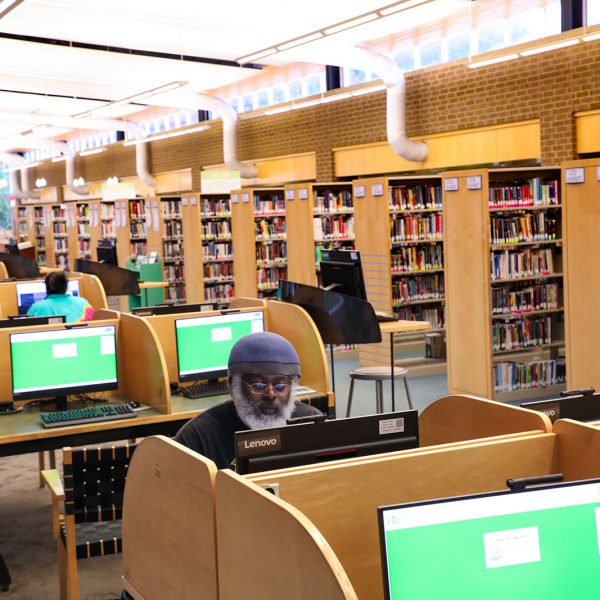 A large open space including a line of desks with computers, many in use, and rows of bookshelves across an aisle