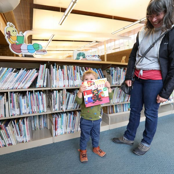 Parent with a small child holding up a book in front of a shelf full of children's books