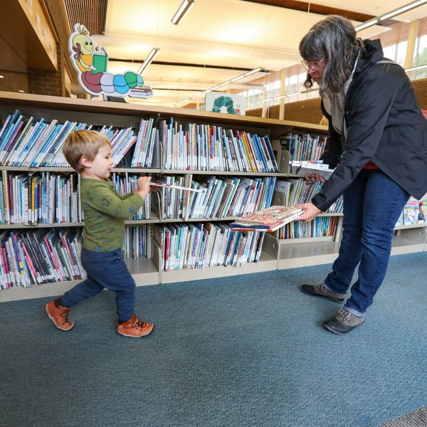 Child hurrying to add a book to a stack in his mother's hands